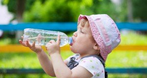child drinking bottled water